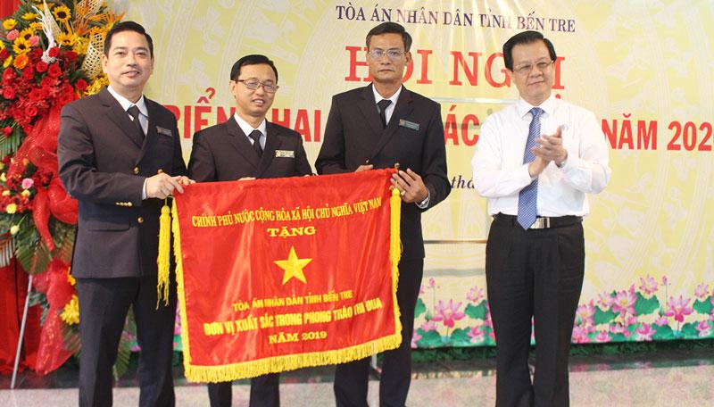 Phó chánh án Tòa án nhân dân tối cao Lê Hồng Quang (bìa phải) trao cờ thi đua của Chính phủ cho đại diện lãnh đạo Tòa án nhân dân tỉnh. Ảnh: Huỳnh Đức