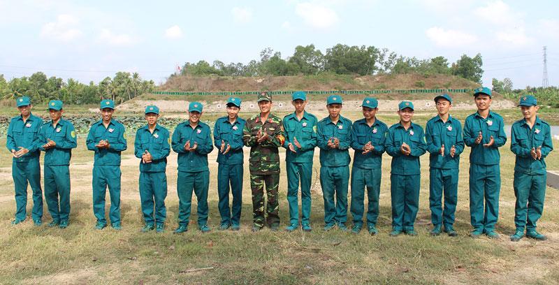 Trung tá Nguyễn Văn Hùng - Phó chỉ huy trưởng, Tham mưu trưởng Ban Chỉ huy Quân sự Mỏ Cày Bắc tặng hoa cho các dân quân tự vệ bắn giỏi.