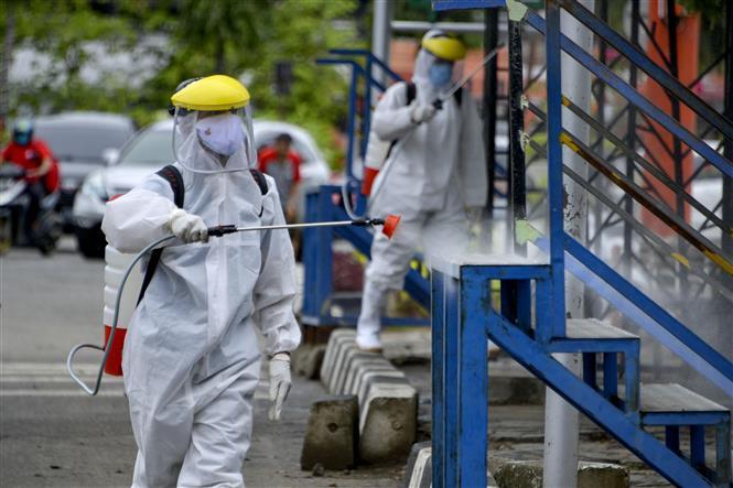 Phun thuốc diệt trùng virus gây dịch COVID-19 tại Indonesia. Ảnh: AFP