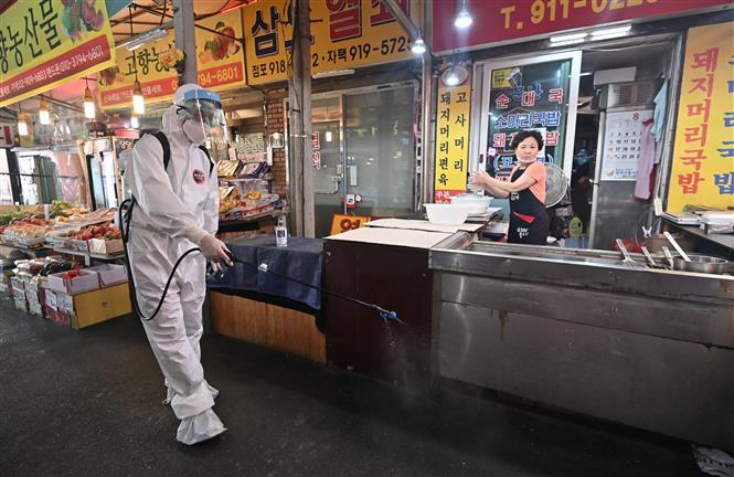 Nhân viên y tế phun thuốc khử trùng nhằm ngăn dịch COVID-19 lây lan tại khu chợ ở Seoul ngày 18-8-2020. Ảnh: AFP/TTXVN
