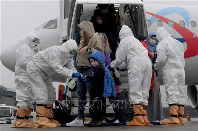 Nhân viên y tế phun thuốc khử trùng cho hành khách nhằm ngừa dịch COVID-19 tại sân bay Kazan, Nga. Ảnh: Xinhua/TTXVN