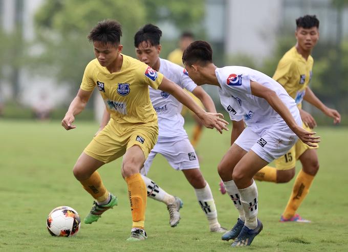Cầu thủ Thanh Hoá (áo vàng) đi bóng trước sự đeo bám của các cầu thủ Đồng Tháp