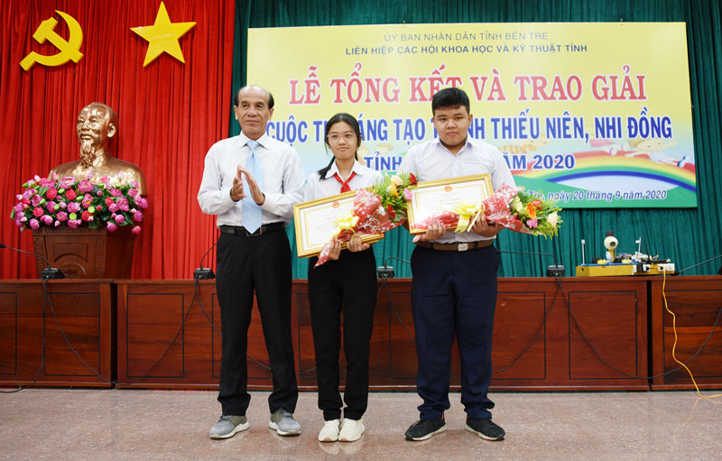 Trao bằng khen của UBND tỉnh cho nhóm học sinh đạt giải nhất cuộc thi.