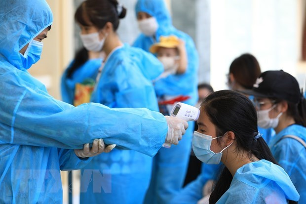 Nhân viên y tế đo thân nhiệt. Ảnh: TTXVN/Vietnam+