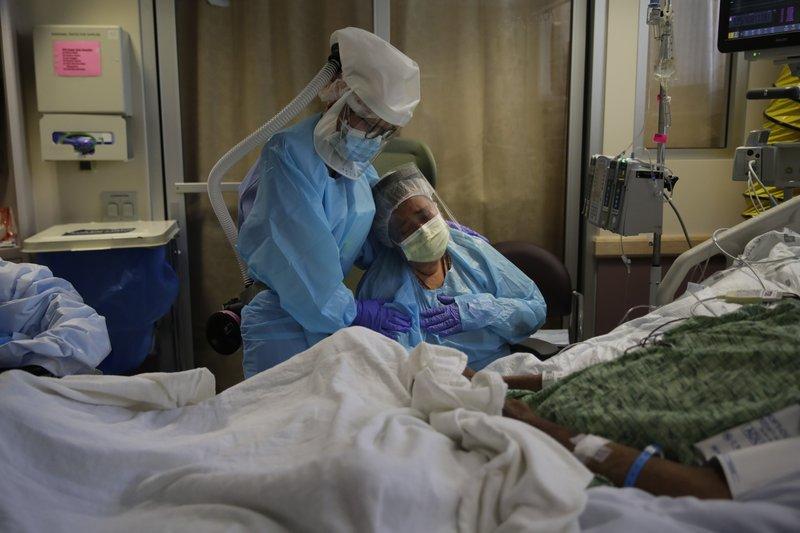 Người phụ nữ khóc thương bên giường bệnh người chồng vừa qua đời vì COVID-19 tại Fullerton, California, Mỹ. Ảnh: AP