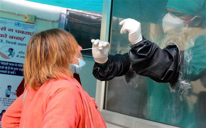 Nhân viên y tế lấy mẫu dịch xét nghiệm COVID-19 cho người dân tại Haridwar, Ấn Độ, ngày 19-9-2020. Ảnh: THX/ TTXVN