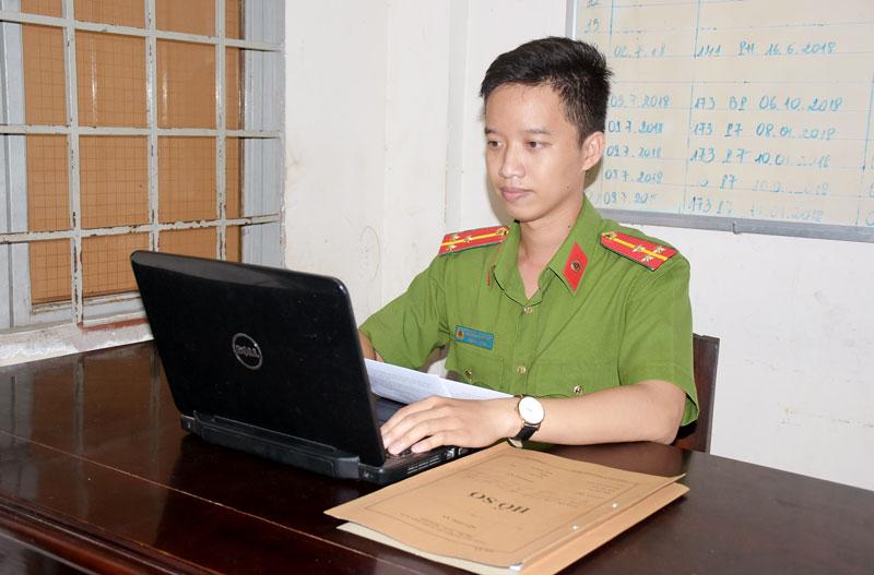 Thượng úy Đỗ Trần Thanh An nghiên cứu hồ sơ tài liệu các vụ án.