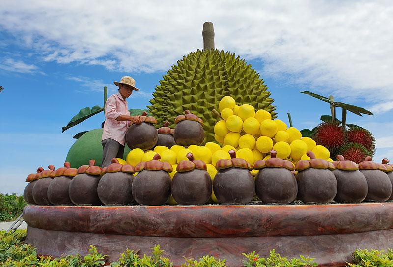 """Anh Bùi Văn Ngưng đang lắp đặt mô hình """"Mâm trái cây đặc sản""""."""