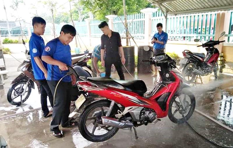 Đoàn viên, thanh niên xã Tân Thiềng, huyện Chợ Lách rửa xe gây quỹ vui Trung thu cho thiếu nhi xã. Ảnh: Đoàn Tân Thiềng