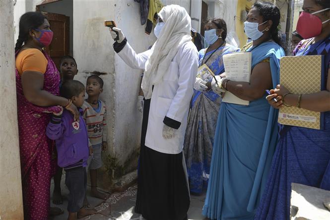 Kiểm tra thân nhiệt nhằm ngăn chặn lây nhiễm COVID-19 tại Hyderabad, Ấn Độ, ngày 24-9-2020. Ảnh: AFP/TTXVN
