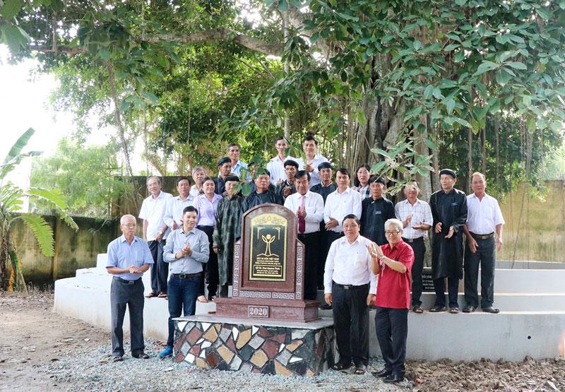 Các đại biểu chụp ảnh lưu niệm tại gốc cây đa di sản Việt Nam tại đình Mỹ Nhơn.