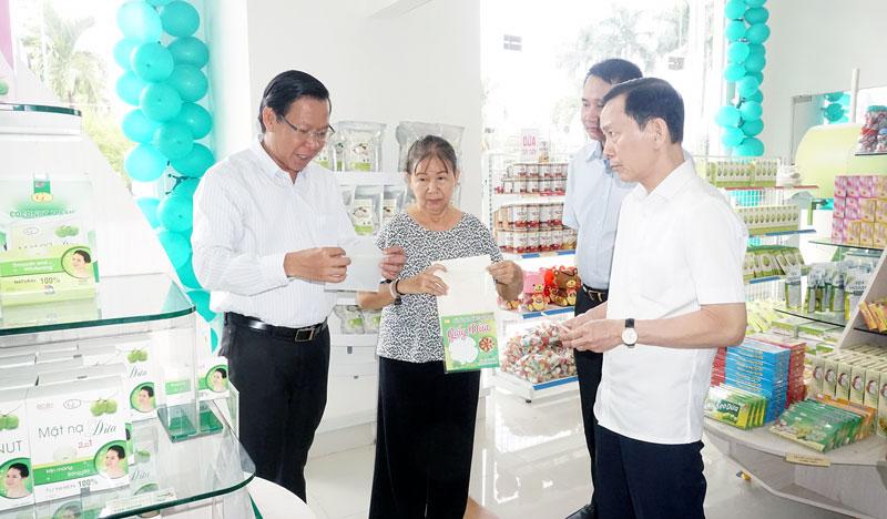 Bí thư Tỉnh ủy Phan Văn Mãi (bìa trái) giới thiệu sản phẩm giấy dừa Thứ trưởng Bộ Kế hoạch và Đầu tư Võ Thành Thống. Ảnh: Q.Hùng