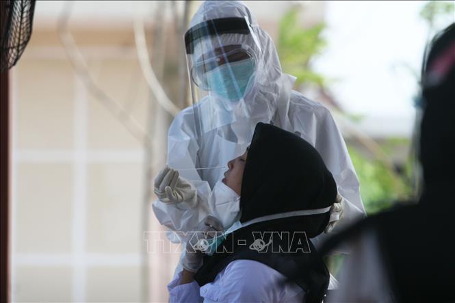 Nhân viên y tế lấy mẫu dịch xét nghiệm COVID-19 cho người dân tại Surabaya, Indonesia ngày 22-9-2020. Ảnh: THX/TTXVN