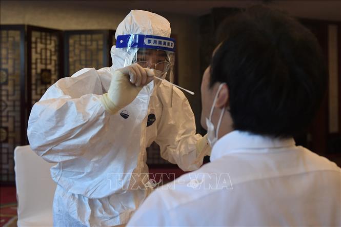 Nhân viên y tế lấy mẫu xét nghiệm COVID-19 tại Bắc Kinh, Trung Quốc ngày 7-9-2020. Ảnh: AFP/TTXVN