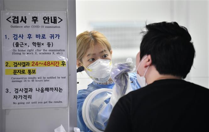 Nhân viên y tế lấy mẫu xét nghiệm COVID-19 cho người dân tại Seoul, Hàn Quốc ngày 18-8-2020. Ảnh: AFP/TTXVN