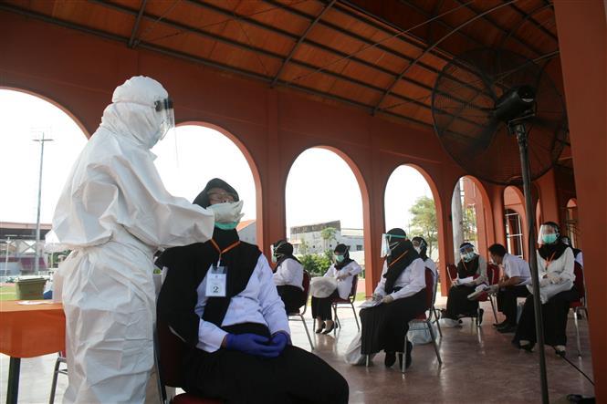 Nhân viên y tế lấy mẫu dịch xét nghiệm COVID-19 cho người dân tại Surabaya, Indonesia, ngày 22-9-2020. Ảnh: THX/ TTXVN