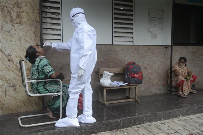 Nhân viên y tế lấy mẫu xét nghiệm COVID-19 cho người dân tại Mumbai, Ấn Độ ngày 25-9-2020. Ảnh: AFP/TTXVN