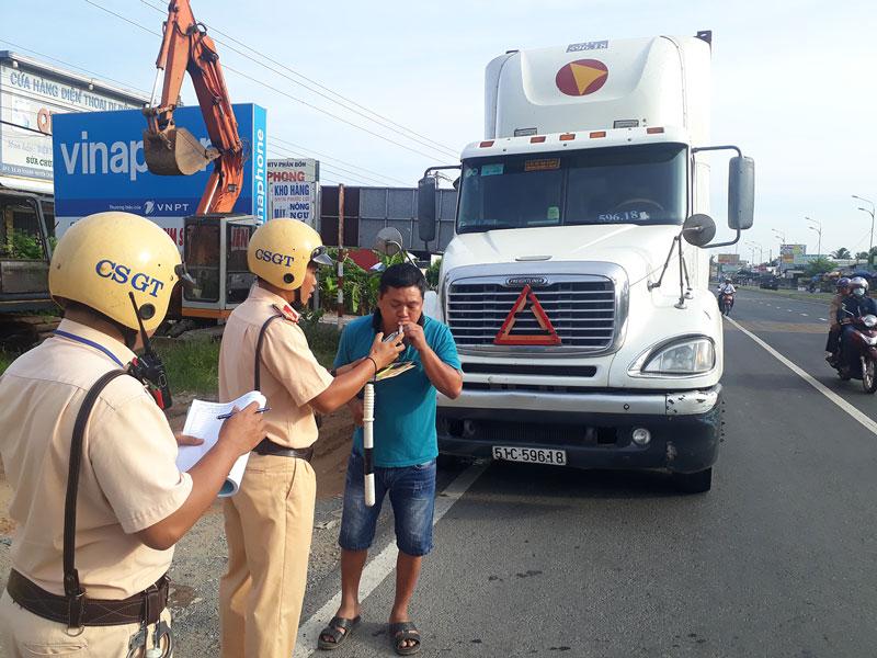 Cảnh sát giao thông kiểm tra nồng độ cồn đối với tài xế xe container.