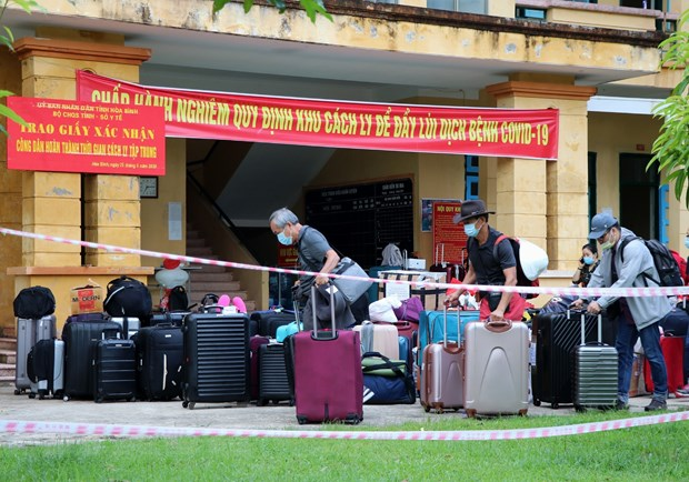Công dân hoàn thành thời gian cách ly vận chuyển đồ đặc cá nhân để trở về địa phương. Ảnh: Thanh Hải/TTXVN