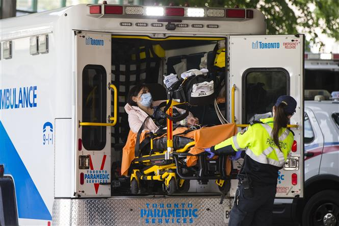 Nhân viên y tế chuyển bệnh nhân COVID-19 tới bệnh viện tại Toronto, Canada, ngày 17-9-2020. Ảnh: THX/ TTXVN
