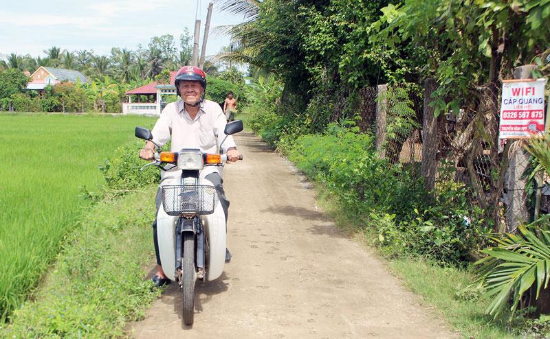 Cựu lão nông Lê Quang Lốc trên đường bê-tông Tổ 15, ấp An Thạnh, xã An Ngãi Trung. Ảnh: Đ. Chính