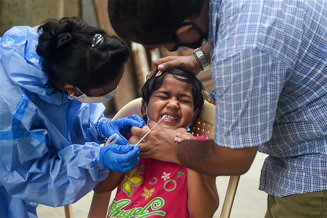 Nhân viên y tế lấy mẫu dịch xét nghiệm COVID-19 cho trẻ em tại Mumbai, Ấn Độ, ngày 3-10-2020. Ảnh: AFP/ TTXVN