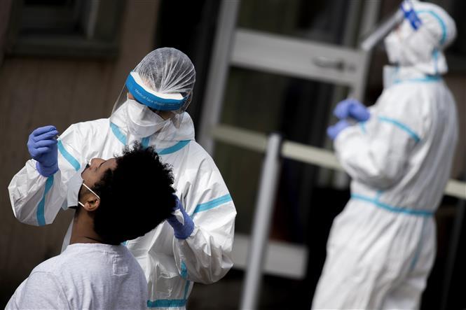 Nhân viên y tế lấy mẫu dịch xét nghiệm COVID-19 cho người dân tại Rome, Italy, ngày 12-10-2020. Ảnh: AFP/ TTXVN