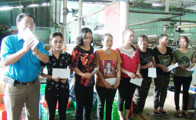Ông Nguyễn Minh Chiến - Chủ tịch Liên đoàn Lao động huyện trao tiền hổ trợ cho công nhân.
