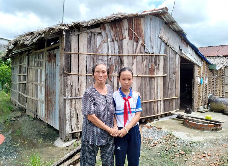 Cháu Trương Ánh Dương cùng với bà nội bên mái nhà vá chằng chịt.