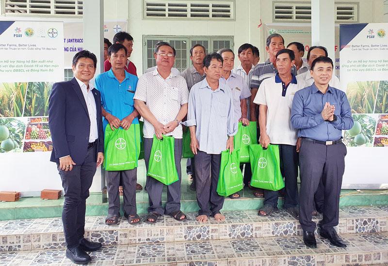Giám đốc Trung tâm khuyến nông quốc gia (thứ hai, phải sang) Lê Quốc Thanh cùng đại biểu trao quà hỗ trợ cho các nông dân.