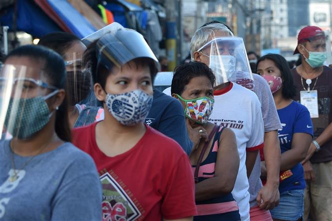 Người dân đeo khẩu trang phòng lây nhiễm COVID-19 khi xếp hàng để vào một chợ ở Manila, Philippines. Ảnh: AFP/TTXVN
