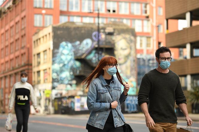 Người dân đeo khẩu trang phòng lây nhiễm COVID-19 tại Manchester, Anh, ngày 16-10-2020/2020. Ảnh: AFP/TTXVN