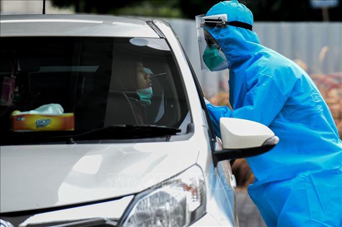 Nhân viên y tế lấy mẫu dịch xét nghiệm COVID-19 cho người dân tại Jakarta, Indonesia ngày 9-10-2020. Ảnh: THX/TTXVN