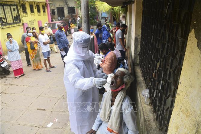 Nhân viên y tế lấy mẫu dịch xét nghiệm COVID-19 cho người dân tại Mumbai, Ấn Độ ngày 12-10-2020. Ảnh: AFP/TTXVN