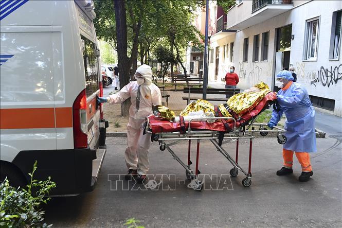 Chuyển bệnh nhân COVID-19 lên xe cứu thương tại Milan, Italy ngày 29-4-2020. Ảnh: AFP/TTXVN