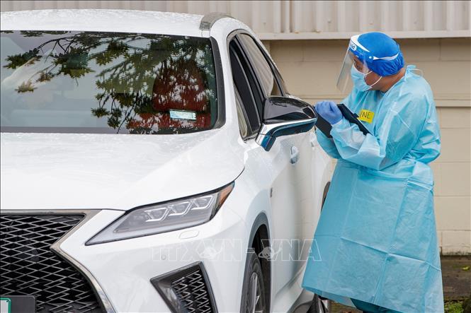Nhân viên y tế lấy mẫu dịch xét nghiệm COVID-19 cho người dân tại Auckland, New Zealand ngày 12-8-2020. Ảnh: AFP/TTXVN