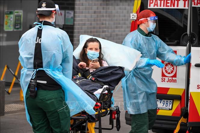 Nhân viên y tế chuyển bệnh nhân mắc COVID-19 lên xe cứu thương tại bang Victoria, Australia ngày 28-7-2020. Ảnh: AFP/TTXVN