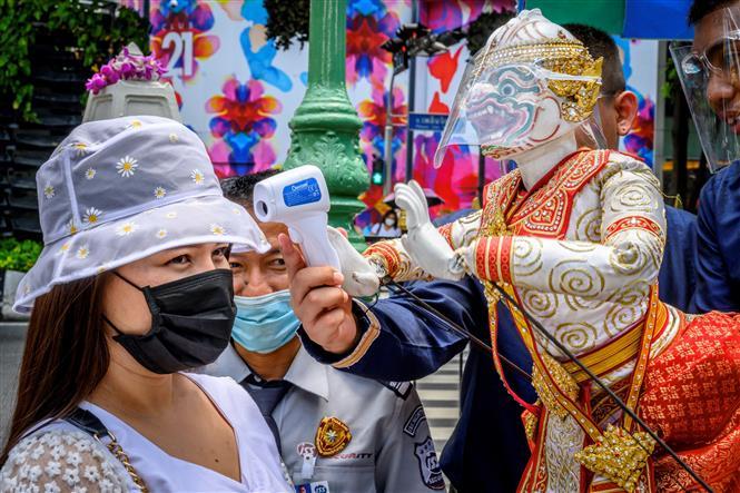 Đo thân nhiệt cho khách thăm quan phòng lây nhiễm COVID-19 tại một ngôi đền ở Bangkok, Thái Lan. Ảnh: AFP/TTXVN