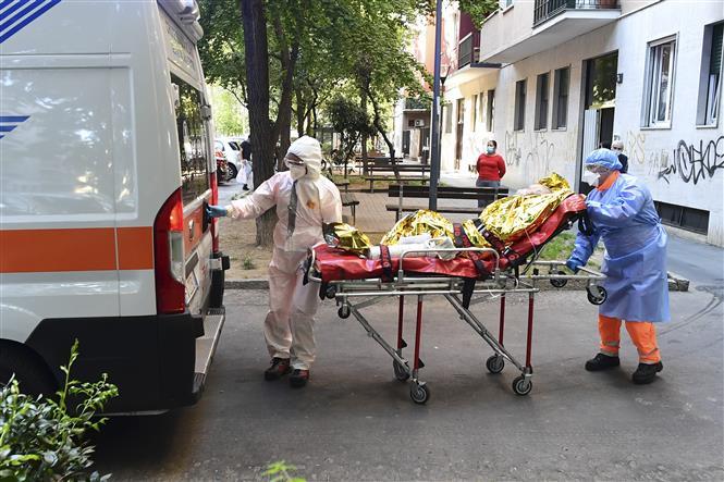 Chuyển bệnh nhân COVID-19 lên xe cứu thương tại Milan, Italy. Ảnh: AFP/ TTXVN