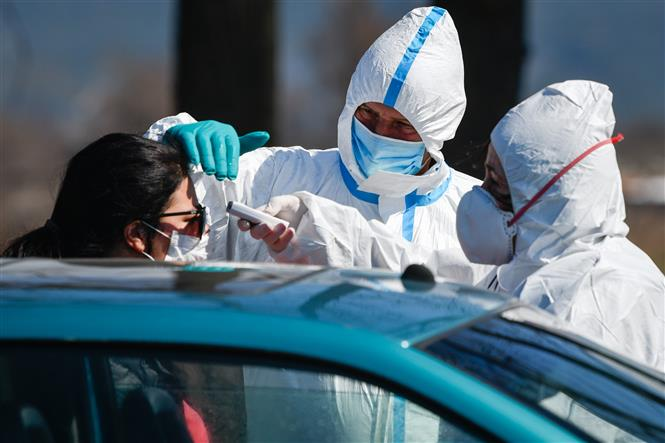 Nhân viên y tế đo thân nhiệt nhằm ngăn chặn sự lây lan của dịch COVID-19 tại Bansko, Bulgaria. Ảnh: AFP/TTXVN