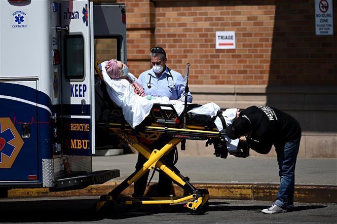 Nhân viên y tế chuyển bệnh nhân COVID-19 tới trung tâm y tế Maimonides ở New York, Mỹ. Ảnh: AFP/ TTXVN