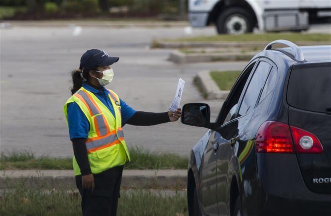 Nhân viên an ninh hỗ trợ người dân tại một điểm xét nghiệm COVID-19 ở Ontario, Canada ngày 1-10-2020. Ảnh: THX/TTXVN