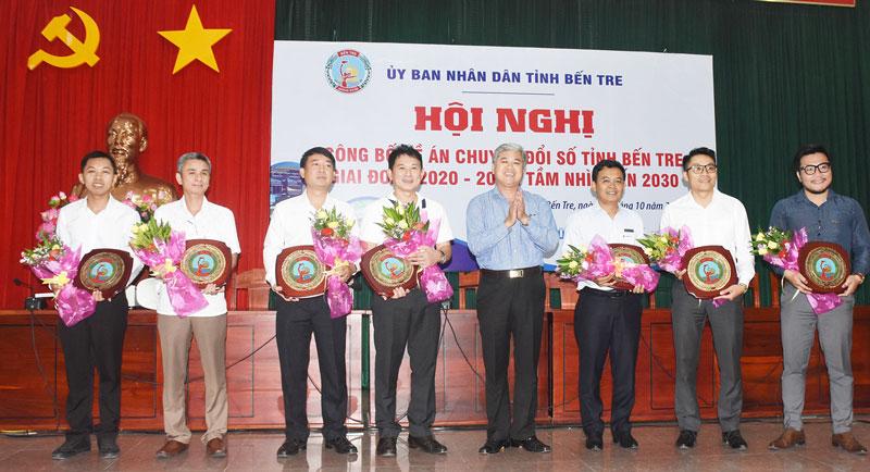 Phó chủ tịch Thường trực UBND tỉnh Nguyễn Văn Đức trao hoa, quà lưu niệm cho các doanh nghiệp, đơn vị trình bày tham luận tại hội nghị.
