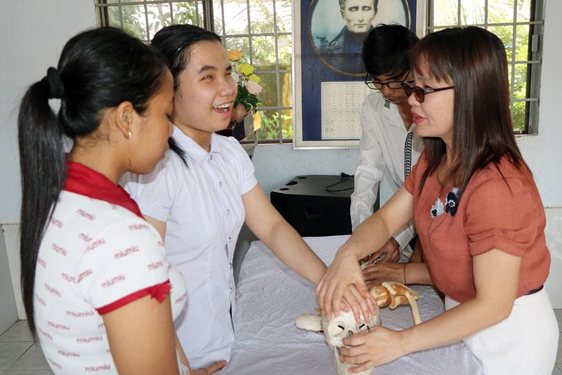 Giảng viên là người khiếm thị hướng dẫn học viên nhận dạng mô hình xương người.
