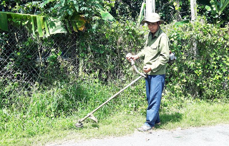 Ông Dương Văn Phính cắt cỏ làm đẹp đường phố.