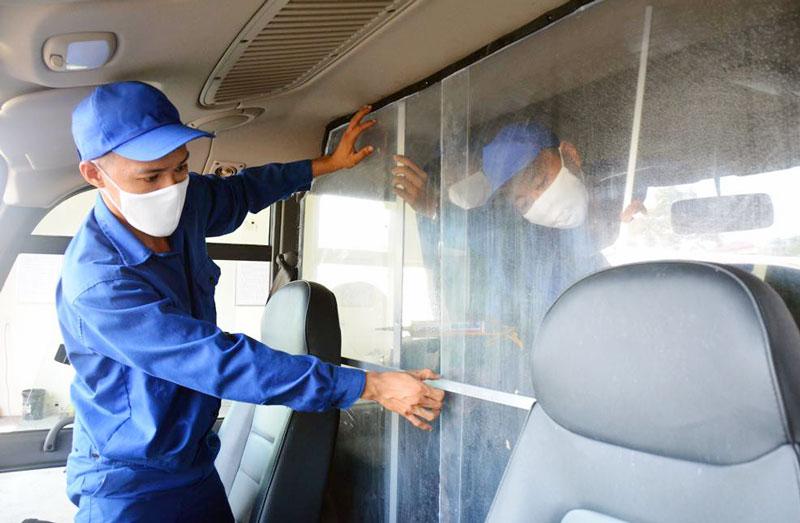 Cán bộ, nhân viên Phòng Kỹ thuật, Bộ Chỉ huy Quân sự tỉnh thực hiện các công đoạn lắp vách ngăn phòng ngừa Covid-19 trên xe. Ảnh: Đặng Thạch