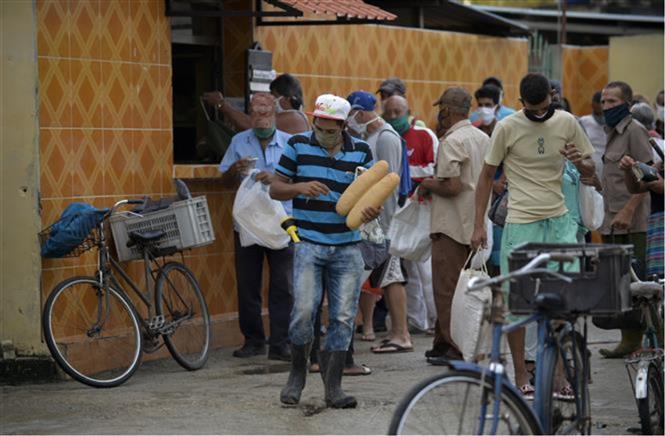 Người dân đeo khẩu trang phòng dịch COVID-19 khi xếp hàng mua bánh mì tại một cửa hàng ở Mayabeque, Cuba ngày 18-6-2020. Ảnh: AFP/TTXVN