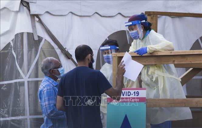 Nhân viên y tế hướng dẫn người dân tại một điểm xét nghiệm COVID-19 ở Toronto, Canada ngày 25-9-2020. Ảnh: THX/TTXVN