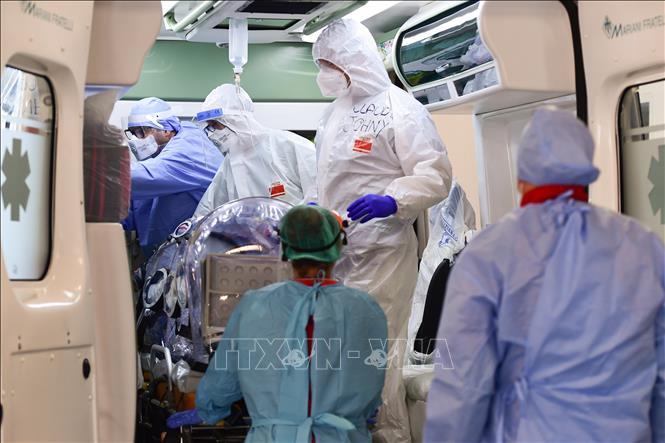Nhân viên y tế chuyển bệnh nhân nhiễm COVID-19 tới bệnh viện ở Milan, Italy. Ảnh: AFP/TTXVN