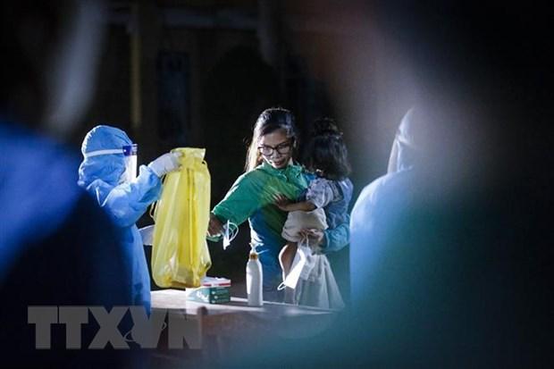 Các công dân thực hiện sát khuẩn, thay khẩu trang và nhận đồ dùng sinh hoạt trước khi vào phòng cách ly theo dõi COVID-19. Ảnh: Trọng Đạt/TTXVN